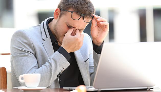 Man met pijn aan zijn ogen achter zijn laptop